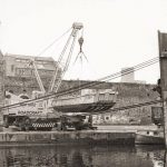 Landing craft being lowered into dock with 25t Coles crane